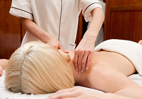A woman in a retro styled spa receiving a shoulder massage